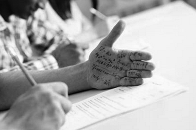 Student copying from what is written on his hand